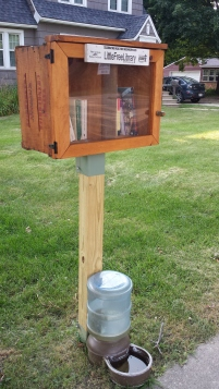 An example of a little lending library with dog water bowl.
